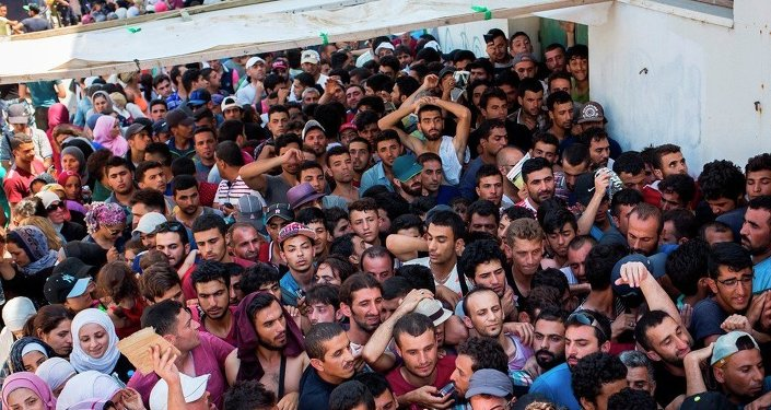 Syrian migrants and refugees gather at a makeshift migrant detention center at Kos' abandoned football stadium after crossing from Turkey, at the southeastern island of Kos, Greece, Wednesday, Aug. 12, 2015.