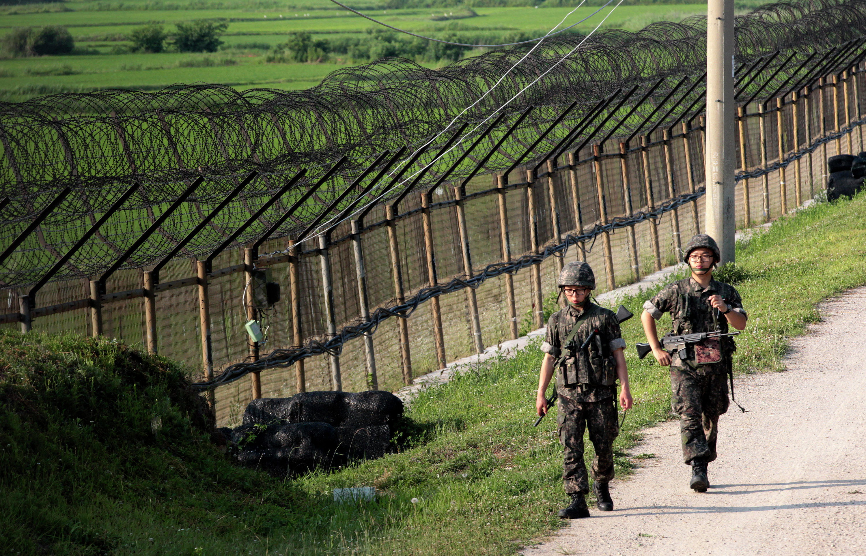 In this June 30, 2014 file photo, South Korean army soldiers patrol through the military wire fence in Paju, near the border with North Korea, South Korea