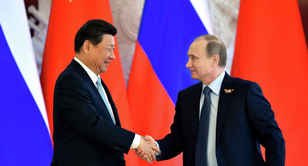 Russian President Vladimir Putin (R) shakes hands with his Chinese counterpart Xi Jinping