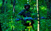 An infantryman, with the Grand Dutches Birute Uhlan Battalion, Lithuanian Armed Forces, patrols the woods for mock enemy troops during exercise Saber Strike, at a training area near Rukla, Lithuania June 15, 2015