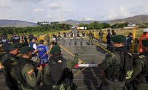 Colombian policemen stand guard in front of the border with Venezuelan policemen Bolivarianos near Villa del Rosario village, August 27, 2015