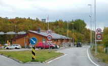 The Norwegian border crossing station at Storskog. The exact border is between the two pillars behind the black van. There is a Russian station further away.