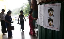 People line up as they leave their slippers near a wanted poster for the main suspect of a deadly bomb blast in Bangkok, Thailand, put up by local authorities at Shwedagon pagoda in Yangon, Myanmar August 25, 2015