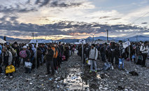 Migrants and refugees wait to board a train near Gevgelija in southern Macedonia after crossing the Greek-Macedonian border on September 27, 2015