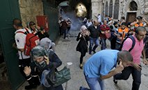 Palestinian protesters run away as Israeli police throw a stun grenade in Jerusalem's Old City September 28, 2015
