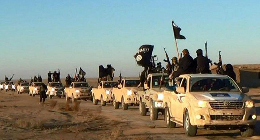 In this undated file photo released by a militant website, which has been verified and is consistent with other AP reporting, militants of the Islamic State group hold up their weapons and wave its flags on their vehicles in a convoy on a road leading to Iraq, while riding in Raqqa city in Syria