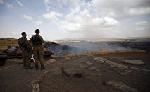 Israeli soldiers watch the flames on a mountain side in the El-Rom settlement in the Israeli-annexed Golan Heights on June 28, 2015