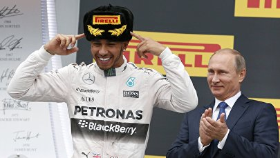 Russian President Vladimir Putin (R) watches as Mercedes Formula One driver Lewis Hamilton of Britain celebrates after winning the Russian F1 Grand Prix in Sochi, Russia, October 11, 2015