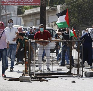 Palestinian protesters take up position during clashes with Israeli troops in the West Bank city of Hebron October 13, 2015