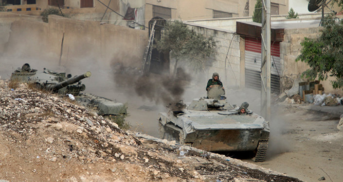 A Syrian APC is followed by a tank in Harasta, northeast of Damascus, Syria, Thursday, Oct. 22, 2015