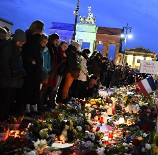 A banner reading 'We are Paris ' is pictured among candles and flowers in front of the Brandenbourg Gate outside the French embassy in Berlin, on November 14, 2015 a day after deadly attacks in Paris