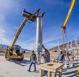 A worker steadies a mock B61-12 as it begins its trip via forklift to the barrel of Sandia National Laboratories' Davis gun, which will fire the test assembly into a pool of water as part of experiments for the B61-12 Life Extension Program