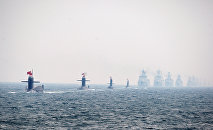 Four Chinese Navy submarines (L) and warships attend an international fleet review to celebrate the 60th anniversary of the founding of the People's Liberation Army Navy on April 23, 2009 off Qingdao in Shandong Province