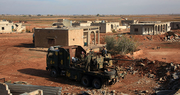 Syrian army soldiers stand on a vehicle carrying heavy artillery  in the village of Akoula near the airport of Kweyris, in the northern Syrian province of Aleppo, after they re-took the area from the control of Daesh . file photo