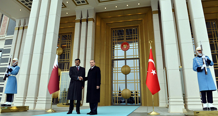 Turkish President Recep Tayyip Erdogan, right, and Qatar's Emir Sheikh Tamim bin Hamad Al-Thani shake hands at the entrance of new presidential palace in Ankara, Turkey, Friday, Dec. 19, 2014