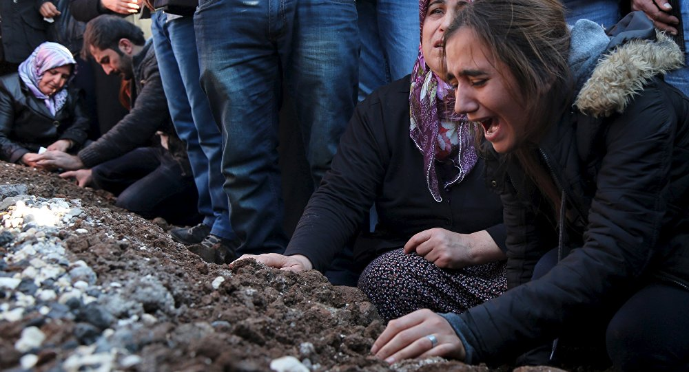 Relatives of Siyar Salman mourn over his grave during a funeral ceremony in the Kurdish dominated southeastern city of Diyarbakir, Turkey, December 15, 2015. According to local media, Salman, a 19-year old man, was killed on Monday in Diyarbakir during a protest against the curfew in Sur district.