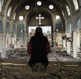 File Photo: A resident of a village in the province of al-Hasake in the north-east of Syria prays in St. George's Church destroyed by Daesh terrorists.