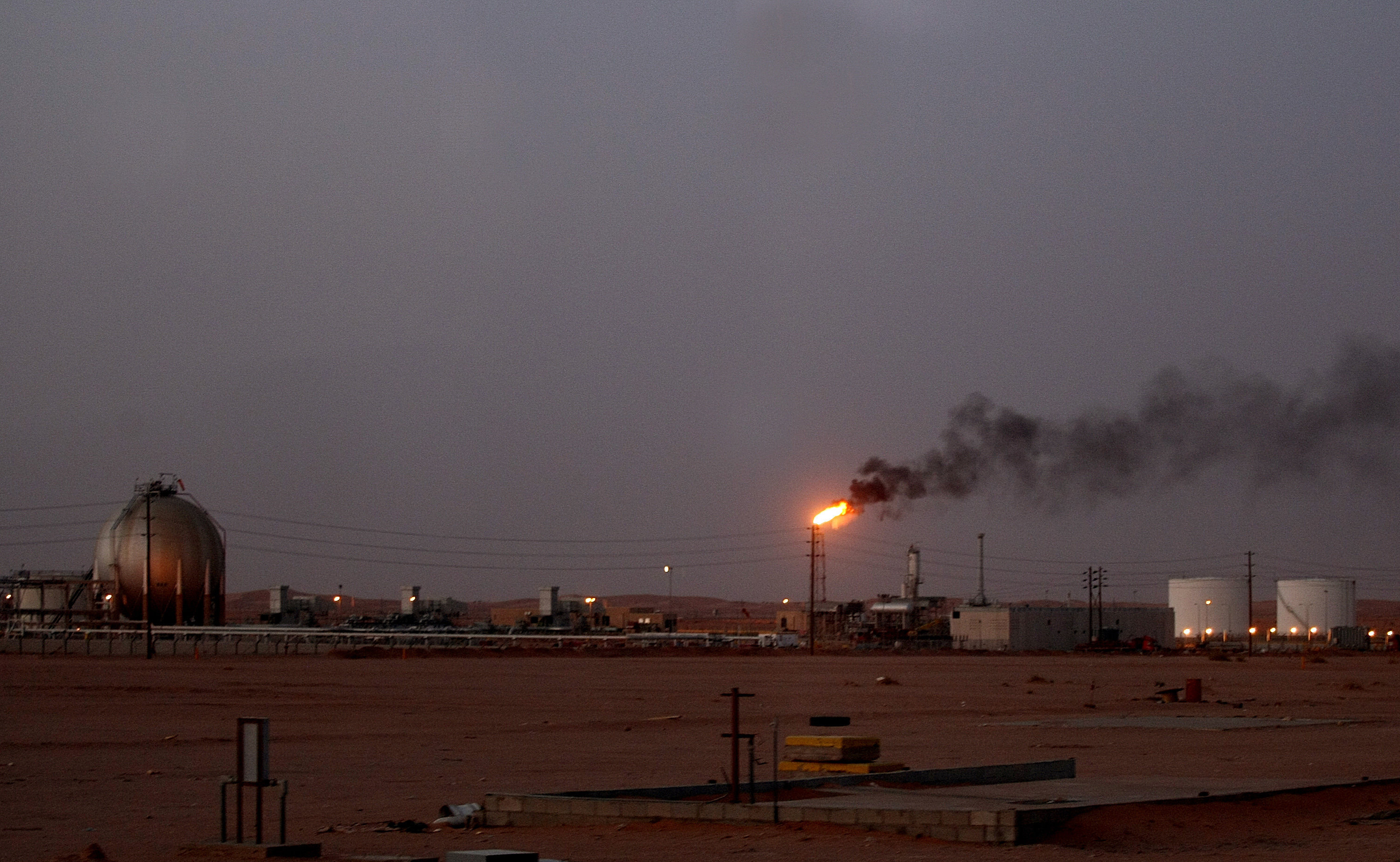 A flame from a Saudi Aramco (the national oil company) oil installation known as Pump 3 burns brightly during sunset in the Saudi Arabian desert near the oil-rich area Al-Khurais, 160 kms east of the capital Riyadh