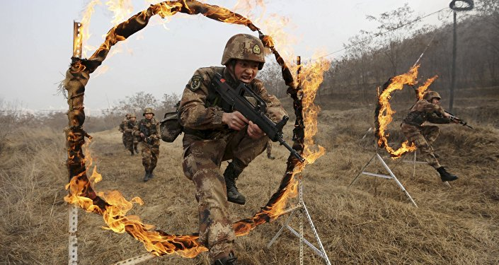 Soldiers of People's Liberation Army (PLA) Lanzhou Military Region jump through a burning obstacle during a training session at a military base in Tianshui, Gansu province, China, January 6, 2016
