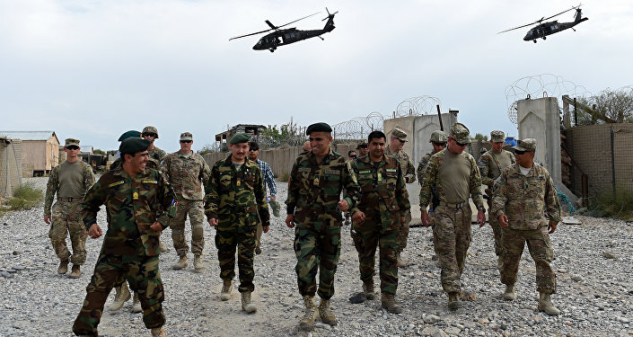 US army and Afghan National Army (ANA) soldiers walk as a NATO helicopter flies overhead