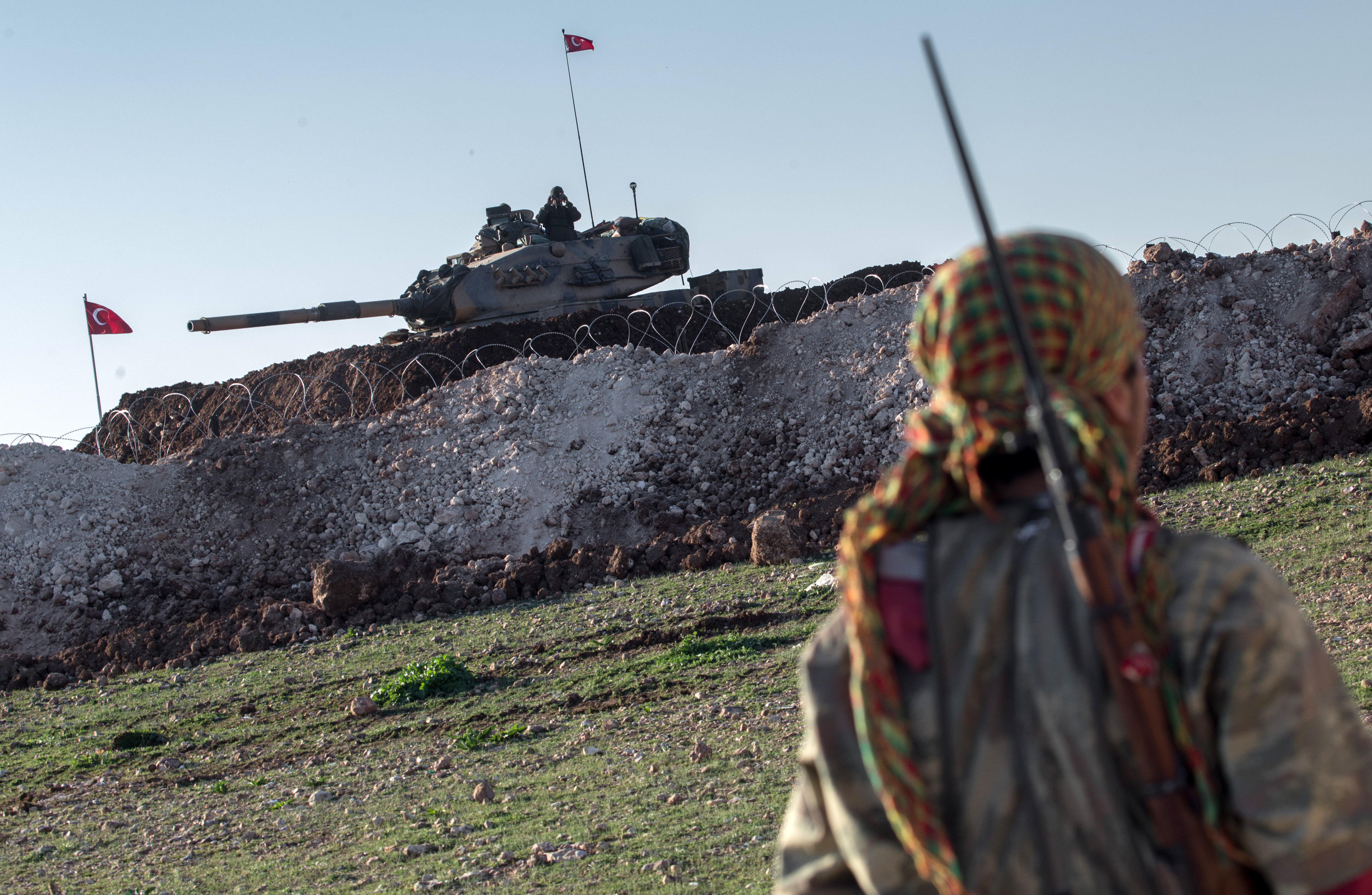 A Syrian Kurdish militia member of YPG patrols near a Turkish army tank as Turks work to build a new Ottoman tomb in the background in Esme village in Aleppo province, Syria. (File)