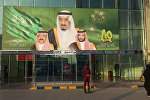 FILE -- In this Dec. 14, 2015 file photo, images of King Salman, center, Crown Prince Mohammed bin Nayef , left, and Deputy Crown Prince Mohammed bin Salman hang at the entrance of a shopping center in Riyadh, Saudi Arabia to mark the country's 85th anniversary
