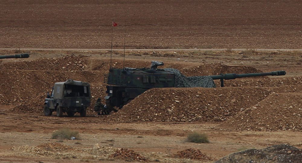 Men watch fighting across the border in Kobani from a hilltop on the outskirts of Suruc, Turkey, backdropped by Turkish army artillery positions near the Turkey-Syria border, Sunday, Oct. 26, 2014