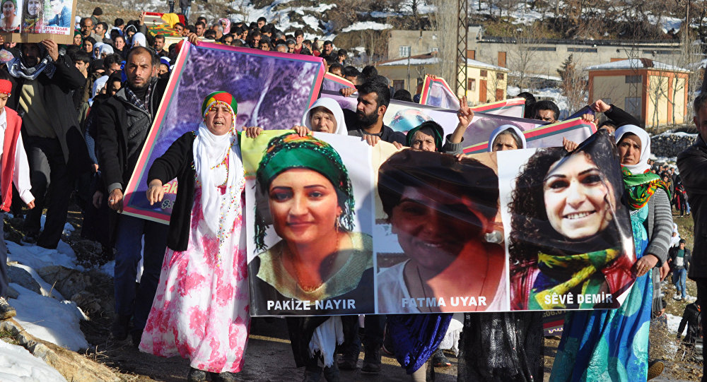 People hold pictures of victims from Cizre and Silopi killed during curfews during a funeral on January 12, 2016, in Sirnak