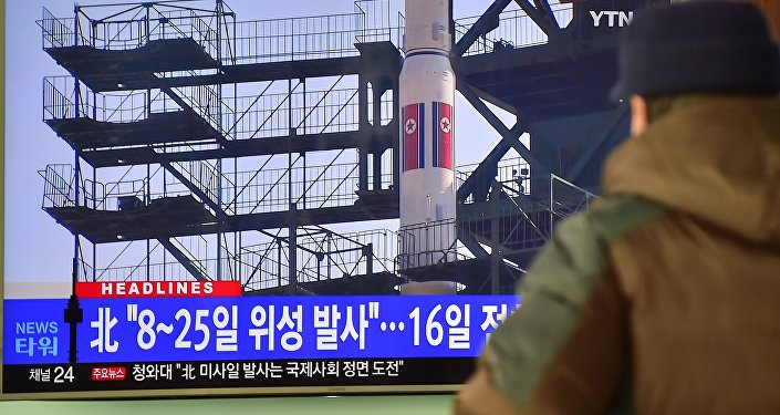 A man watches a news report on North Korea's planned rocket launch as the television screen shows file footage of North Korea's Unha-3 rocket which launched in 2012, at a railway station in Seoul on February 3, 2016