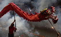 Revellers explode firecrackers near dragon dancers as they celebrate Chinese New Year in Manila's Chinatown, Philippines