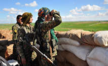 Members of the Kurdish People's Protection Units (YPG) monitor the positions of Islamic State (IS) group in the Syrian town of Ras al-Ain, close to the Turkish border on March 13, 2015
