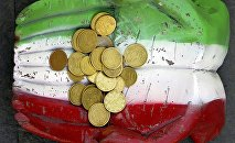 Euro coins seen on the figure of a pair of hands, which are painted in Italy's colour national colours, on the ground in downtown Rome.