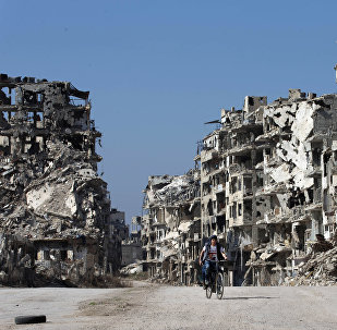A Syrian boy rides a bicycle through a devastated part of the old city of Homs, Syria, Friday, Feb. 26, 2016