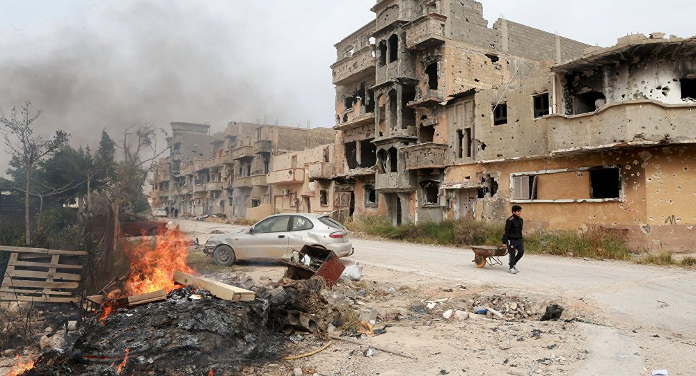 A man pulls a wheelbarrow past destroyed buildings after clashes between military forces loyal to Libya's eastern government and Islamist fighters, in Benghazi, Libya, February 28, 2016