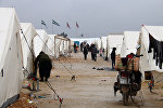 Displaced Syrians fleeing areas in the northern embattled province of Aleppo, walk past tents at the Bab al-Salama camp, set up outside the Syrian city of Azaz on Syria's northern border with Turkey on February 12, 2016