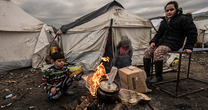 Young migrants get warm around a brazier in the migrants camp of Grande-Synthe, near Dunkirk, on January 20, 2016, where almost some 2,500 migrants and refugees live, mostly Iraqi Kurds and Syryans