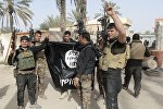 Iraqi security forces celebrate as they hold a captured flag of the Islamic State group (File)