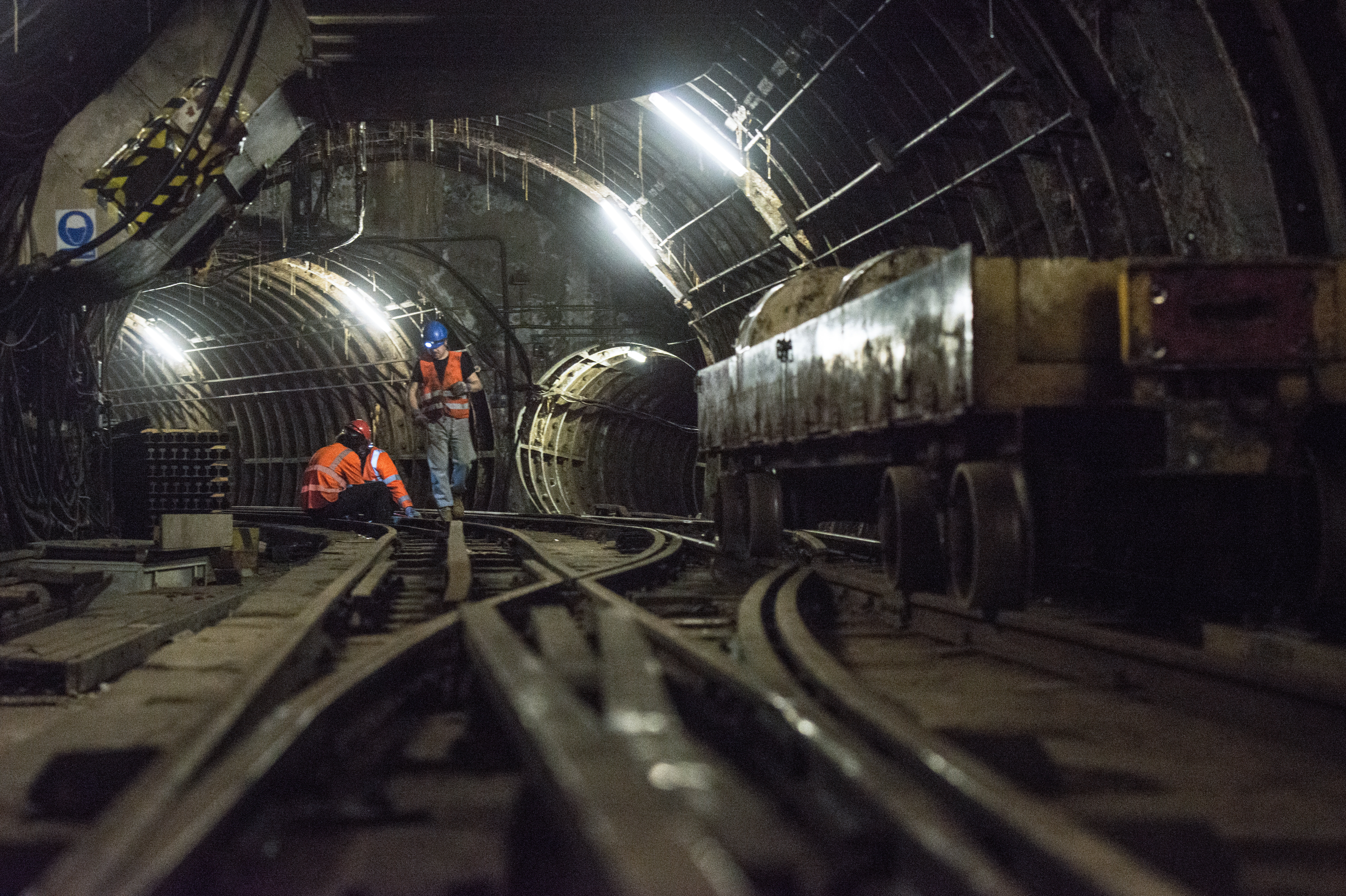 Workers sit on the underground tracks of the Mail Rail, the old rail system that transported mail between sorting offices, as work starts to turn it into a heritage attraction at the new Postal Museum in London