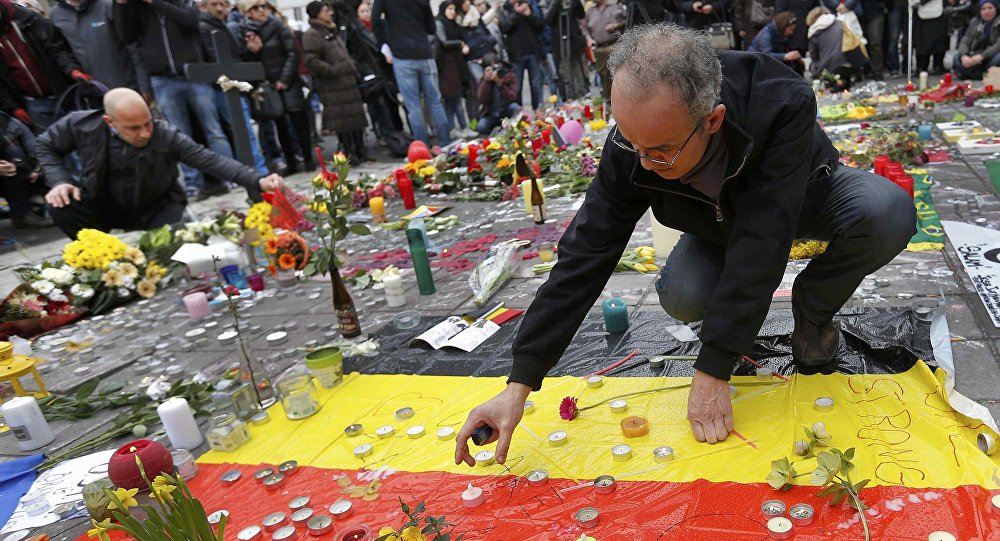 Men place a candles on a street memorial following Tuesday's bomb attacks in Brussels, Belgium, March 23, 2016
