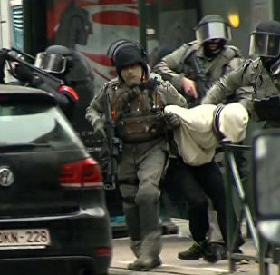 In this framegrab taken from VTM, armed police officers escort Salah Abdeslam to a police vehicle during a raid in the Molenbeek neighborhood of Brussels, Belgium, Friday March 18, 2016