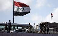People walk near a Syrian national flag at the President bridge in Damascus, Syria March 14, 2016
