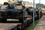 M1A2 Abrams Main Battle Tanks are lined up on rail cars