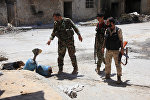 Syrian army soldiers check unexploded homemade rockets during a patrol in Aleppo (File)