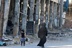 Residents walk past damaged buildings in the rebel held area of Aleppo's Bab al-Hadeed district, Syria, June 27, 2016.