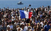 A French flag flies among the crowd as people gather in front of the Monument du Centenaire during a minute of silence on the third day of national mourning to pay tribute to victims of the truck attack along the Promenade des Anglais on Bastille Day that killed scores and injured as many in Nice, France, July 18, 2016.