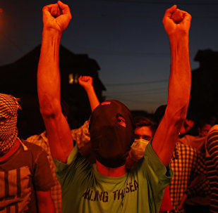 A masked Kashmiri shouts slogans during a in a torch light protest in Srinagar, Indian controlled Kashmir, Thursday, July 21, 2016.