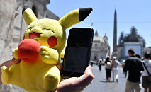 A gamer holds a Pokemon mascot and his mobile phone as he plays with the Pokemon Go application in central Rome on July 19, 2016