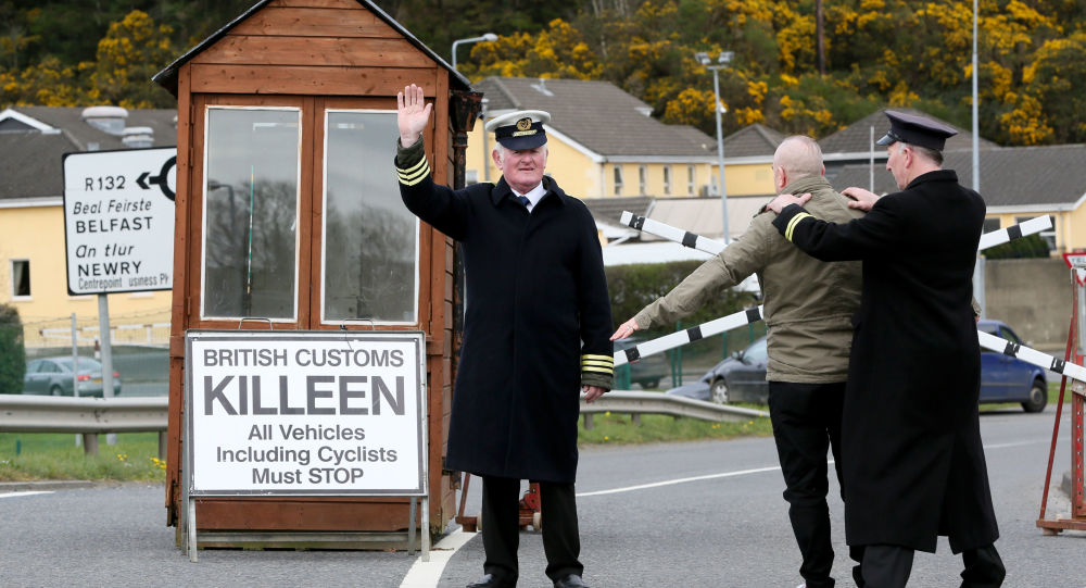 Two protesters dressed as border guards 'search' another protester in a stunt during a protest against any border between Ireland and Northern Ireland because of Brexit gather at the Carrickcarnan border between Newry in Norther Ireland and Dundalk in the Irish Republic on March 30, 2019