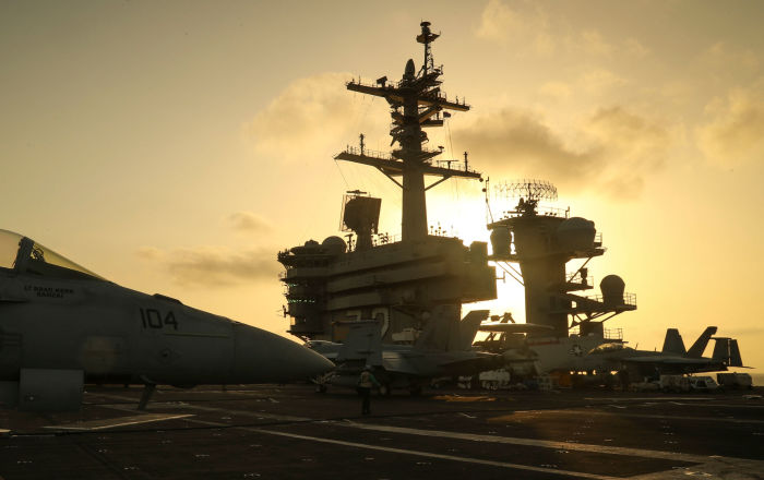 The sun sets behind the U.S. Navy aircraft carrier USS Abraham Lincoln, in Arabian Sea, June 3, 2019. Picture taken June 3, 2019