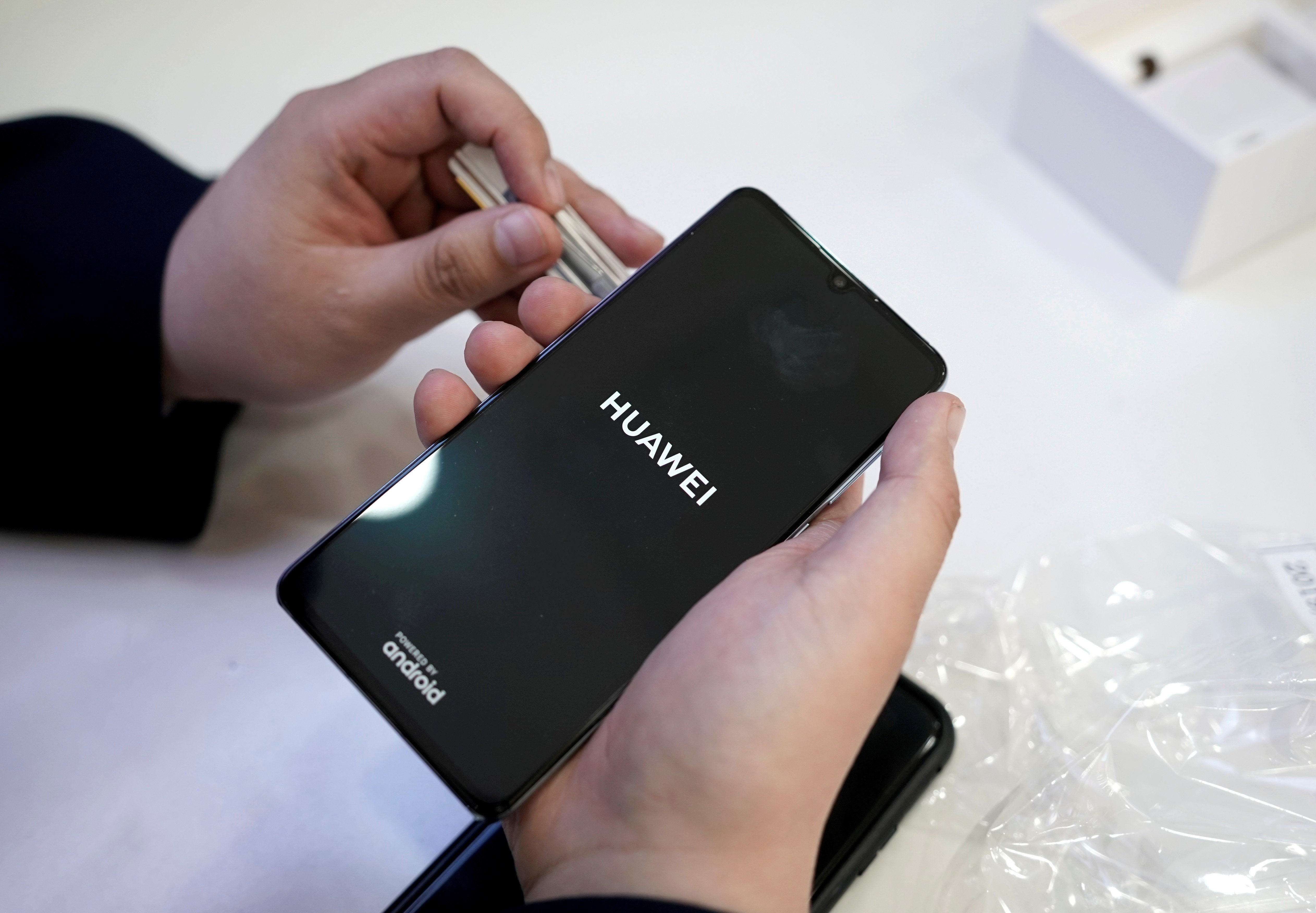 A salesman turns on a new Huawei P30 smartphone for a customer in Beijing